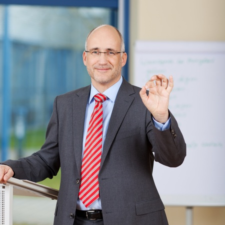 Portrait of confident businessman gesturing OK sign while standing in office photo