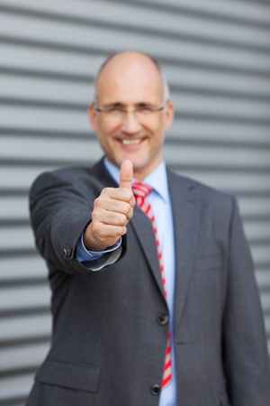 thumbs up sign: Portrait of happy businessman gesturing thumbs up against shutter