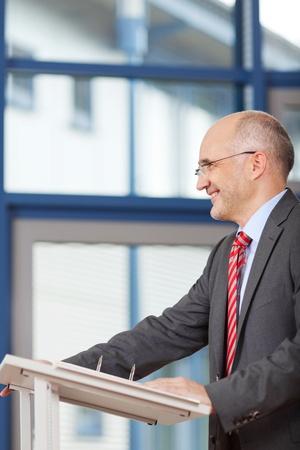 the speaker: Vista lateral del hombre de negocios maduro de pie en el podio en la oficina Foto de archivo