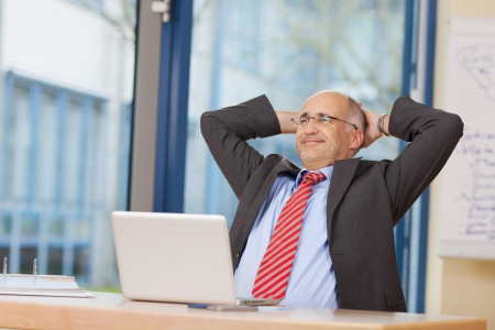 relaxed business man: Relaxed businessman with hands behind head sitting at office desk