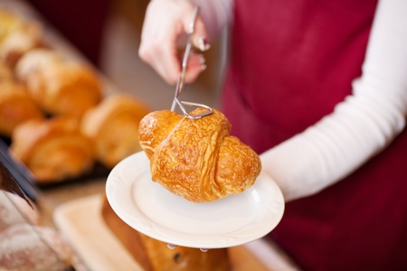 breadloaf: waitress serving croissant in a coffee house