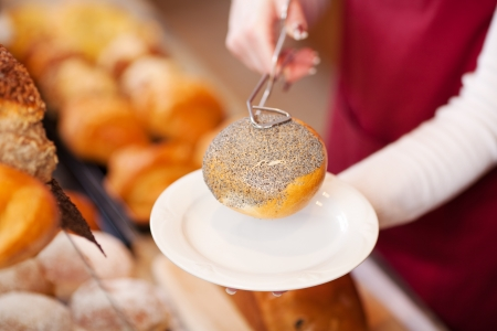 woman in bakery serving bread roll on a plate photo