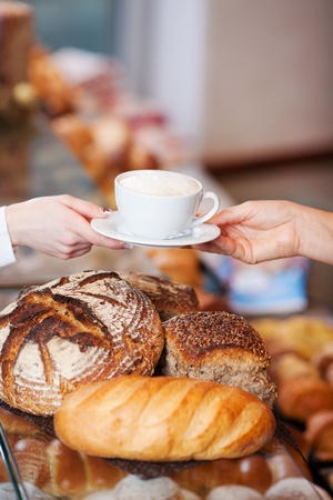 breadloaf: two woman´s hands passing a cup of cappuccino in bakery