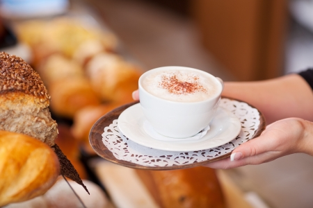 breadloaf: saleswoman passing cappuccino over the counter in a bakery