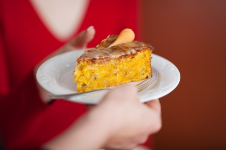 carot: woman´s hand serving carot cake at coffee house