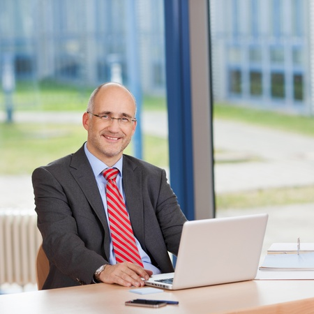 Portrait of confident businessman with laptop sitting at office desk photo
