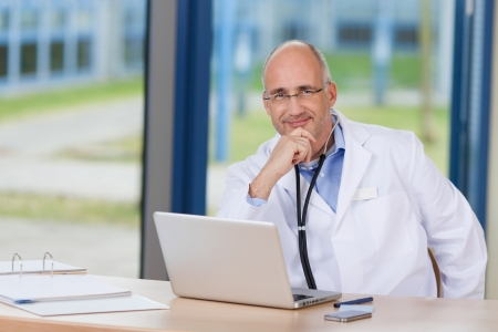 Portrait of confident male doctor with hand on chin and laptop on desk in clinic Banco de Imagens