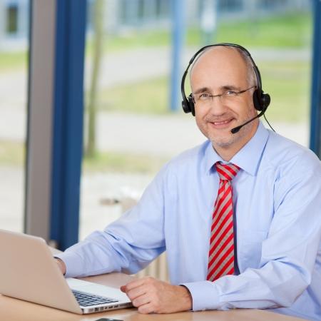 Ritratto di fiducia maschio servizio clienti esecutivo indossa auricolare mentre si utilizza laptop alla scrivania in ufficio Archivio Fotografico