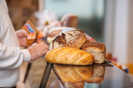 breadloaf: Midsection of male customer with breads placed on counter in bakery