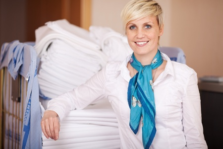 Portrait of smiling female housekeeper in stock room photo