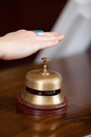 Closeup of clients hand over bell at reception in hotel photo