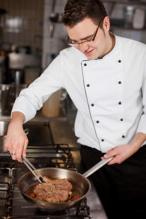 smiling young cook preparing steak in a pan photo