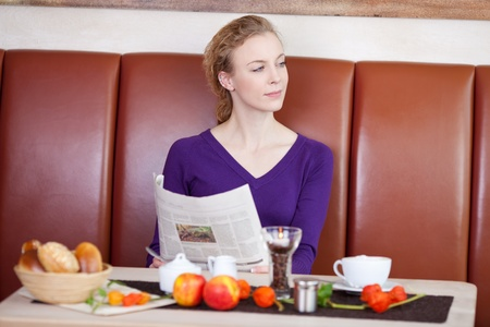 bakery store: Young woman with newspaper looking away at desk in coffee shop