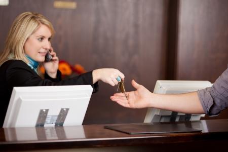 recepcionista: Recepcionista joven que da las llaves a los clientes en la recepción en el hotel