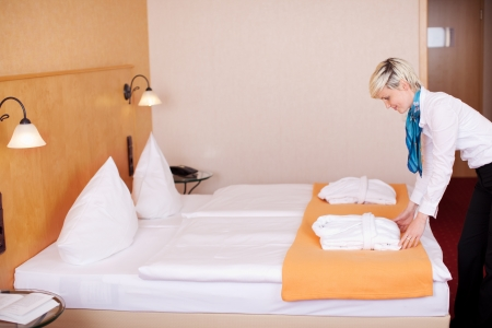 maid making bed in a hotel room photo
