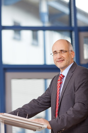 Portrait of confident mature businessman standing in office photo
