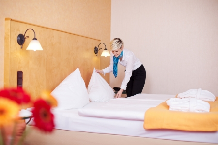 Young blond hair housekeeper making bed in hotel room photo