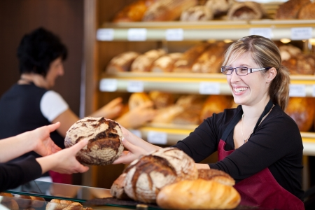 over the counter: friendly saleswoman in bakery passing bread over the counter