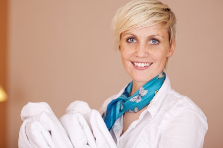 Portrait of smiling female housekeeper with bathrobes photo