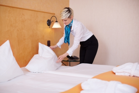 Young female housekeeper making bed in hotel room Stock Photo - 21219310