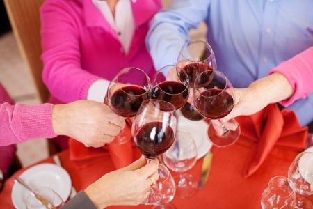 older couple: Closeup of customers toasting wine glasses at restaurant table