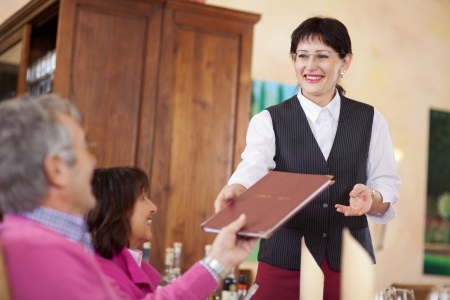 cheerful smiling waitress passing the menu to guest photo