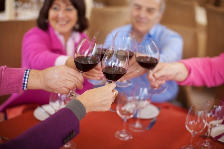 smiling elderly friends saying cheers with red wine