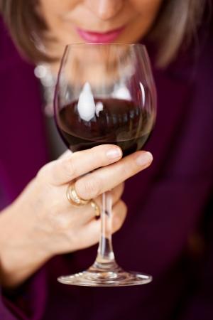 bebiendo vino: Mujer con vaso de vino tinto en el restaurante Foto de archivo