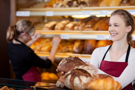 salesgirl: saleswoman in bakery with bread in her hands in front of shelves Stock Photo