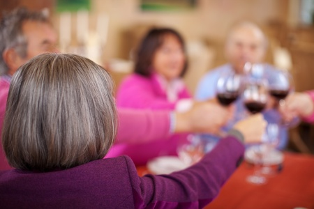 elderly friends celebrating in restaurant, saying cheers with red wine photo