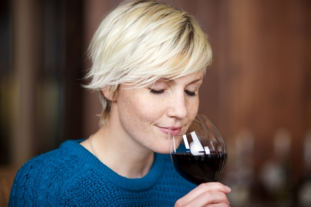 olfato: closeup retrato de joven mujer rubia de beber vino tinto en el restaurante Foto de archivo