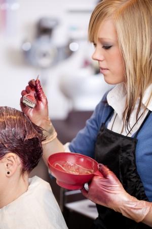 tinte cabello: Peluquería femenina bastante joven o un asistente de aplicar un tinte de pelo de un cliente con un cepillo Foto de archivo