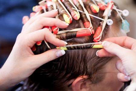 Nahaufnahme der Hände eines weiblichen Friseur eine Dauerwelle machen Rollen des Kunden Haar auf Lockenwickler feinen Rollen oder für eine lockige oder wellenförmige Wirkung