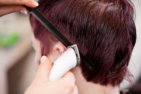 Hairstylist using a razor to trim the hair around a customers ear in a short neat hairstyle Stock Photo - 21222931