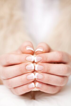 cosmetic lacquer: Woman displaying her beautiful manicured fingernails finished in clear gloss varnish holding the tips of her two hands together