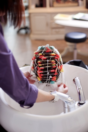 La peluquera y una permanente colocando un heairnet sobre los rulos enrollada en un pelo de los clientes antes de aplicar la loción de permanente