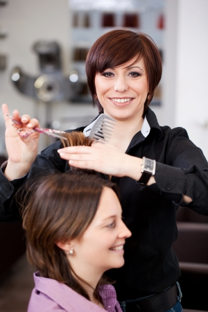 snipping: Hairdresser cutting a womans hair in a professional salon with both women smiling happily