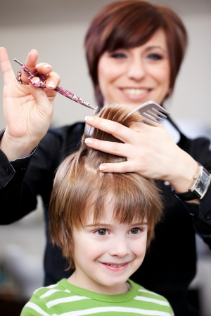 Cute little child getting a haircut from a smiling female hairdresser who is trimming the ends of the hair with scissors