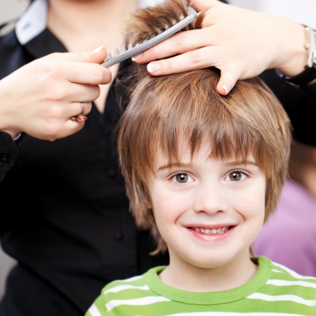 peluqueria: Hermoso ni�o peque�o con grandes ojos expresivos en la peluquer�a con un corte de pelo