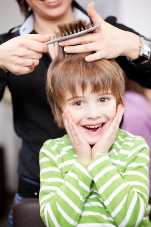 snipping: Cute young child at the hairdresser laughing with his hands to his face as the stylist cuts his hair with scissors