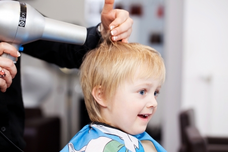 Little child with a look of comical amazement getting a blow dry at the hairdresser from a professional stylist photo