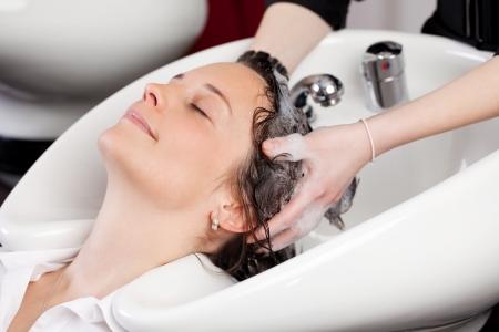 peluqueria: Atractiva mujer sonriendo con los ojos cerrados en el disfrute con un champ� para el pelo en la peluquer�a