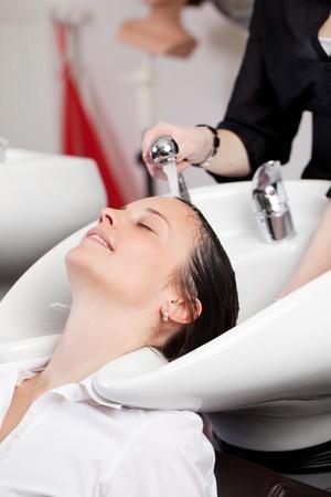 handbasin: Hairstylist giving a hair shampoo at a hand basin in the hair salon to a relaxed woman customer