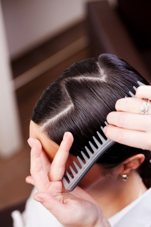 vertex: Closeup view of the hand and comb of a hairstylist combing a new hairstyle on a customer with a zig zag parting Stock Photo