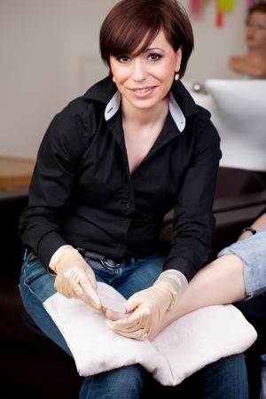 chiropody: Pedicurist in a nail studio or beauty salon sitting with a clients bare foot on her lap smiling up at the camera