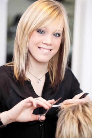 Beautiful smiling young female trainee hairstylist cutting blond hair with scissors in a hair salon photo