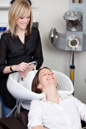 handbasin: Attractive woman enjoying having her hair washed in the hair salon smiling at the hairdresser holding the nozzle
