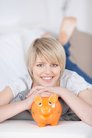 Friendly attractive young blond woman with her cute orange piggy bank lying resting on a sofa with her chin on its back dreaming of her goals and future photo
