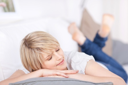 home comfort: Beautiful blond woman sleeping on a sofa lying on her stomach with her head on her arms and a serene expression