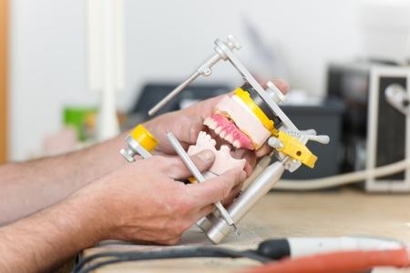 articulator: Closeup of dental technicians hands working with articulator in dental laboratory